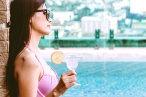 Woman wearing bikini drinking cocktail in swimming pool on summer vacation relaxing at resort spa